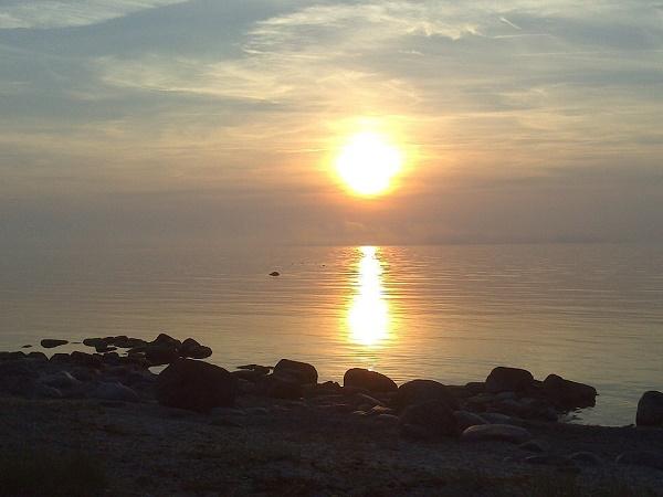 Il tramonto infinito del sole di mezzanotte sull'oceano che bagna la Svezia.