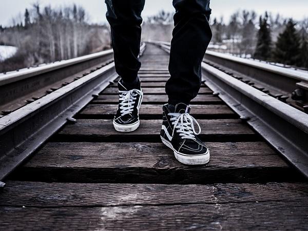 Un ragazzo che cammina lungo le rotaie di un treno, l'emblema del viaggiare da soli.