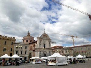 La piazza del Duomo de l'Aquila ha solo qualche impalcatura residua, ma è di nuovo una piazza vera, dove passeggiare, guardare le vetrine e fare il mercato.