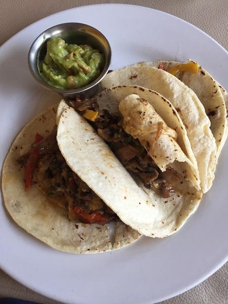 Assaggiate i tacos al pastor, tortillas di mais farcite con carne di maiale allo spiedo, servite con verdure e cipolla.