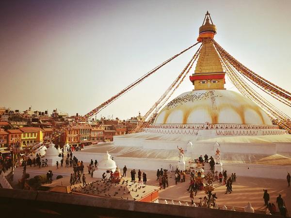 La grande stupa di Boudhanath si anima all'ora della preghiera di una processione di persone di tutte le età, dai tratti somatici tibetani/mongoli, molte delle quali in abiti tradizionali.