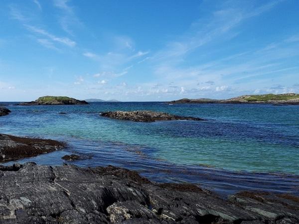 Nel Connemara, l'incantevole Glassilaun Beach con rocce nere che si diramano nell'oceano blu.