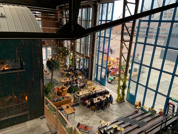 L'NDSM-werf di Amsterdam, ex cantiere navale, oggi ospita edifici modernisti, atelier e locali lungo il fiume IJ.